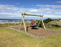 Kids playing on swing by beach